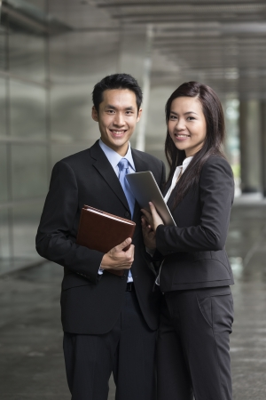 computer office: Portrait of Chinese business man and woman in a modern urban setting.  Stock Photo