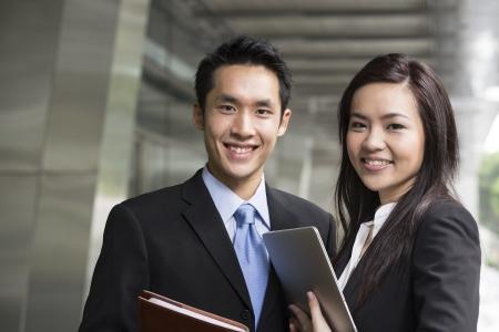 business smile: Retrato de hombre de negocios de China y de la mujer en un entorno urbano moderno.