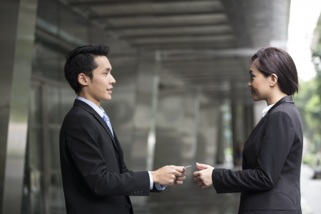 exchanging: Asian Businessman presenting his business card to a businesswoman