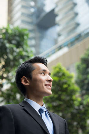 asian businessman: Chinese business man in modern Asian city. Asian businessman smiling & looking away with blurred office buildings as a background.