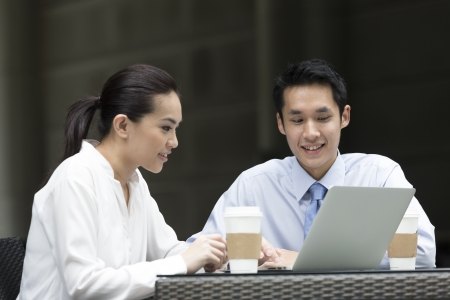 Chinese business Man and woman working together on a laptop outdoors in modern city. photo