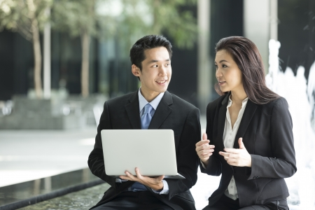 Chinese business Man and woman working together on a laptop outdoors in modern city. Stock Photo