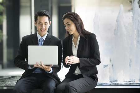 asian business: Chinese business Man and woman working together on a laptop outdoors in modern city. Stock Photo