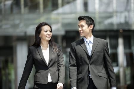 Happy collègues d'affaires chinois marchant à l'extérieur de bureau et de parler les uns aux autres. Banque d'images