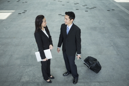 Above view of two Happy Chinese Business colleagues standing outside office & talking to each other. photo