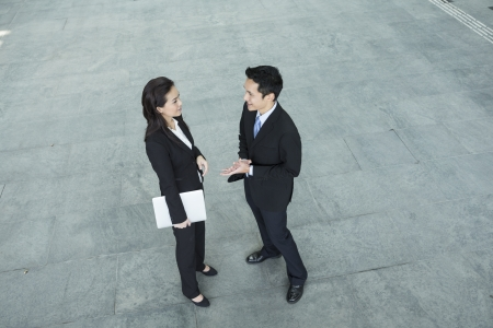 Above view of two Happy Chinese Business colleagues standing outside office & talking to each other. Stock Photo