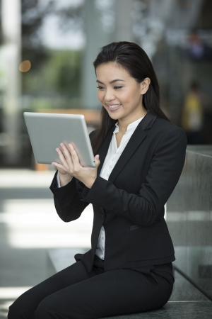 Happy Chinese busines woman using a tablet pc outside photo