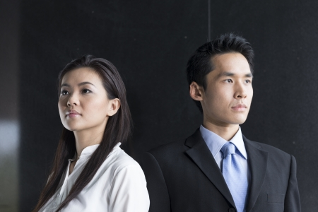 Portrait of two serious Chinese business people standing in front of a black wall.