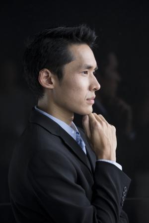 L'homme d'affaires chinois se penchant sur un mur noir. Beau jeune homme d'affaires chinois appuyé contre un mur noir. Banque d'images