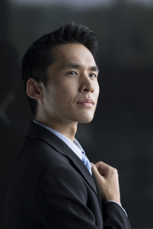 Chinese Business man leaning on a black wall. Handsome young Chinese business man leaning against a black wall.