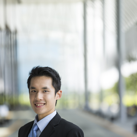 asian businessman: Chinese business man in modern Asian city. Asian businessman smiling & looking at the camera with blurred office buildings as a background. Stock Photo