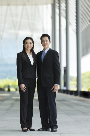 Portrait of Chinese business man and woman in a modern urban setting.  photo