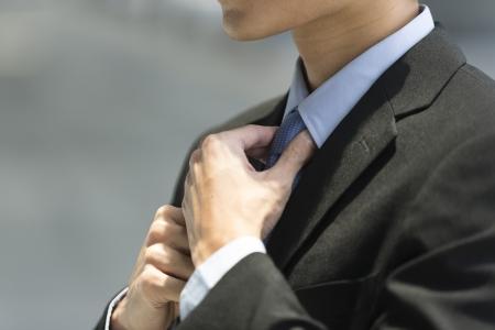 black tie: Primer plano detalle de un hombre de negocios asi�tico que llevaba un traje y ajust�ndose la corbata azul.