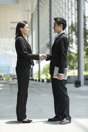 Chinese Businessman and businesswoman shaking hands outside the office photo