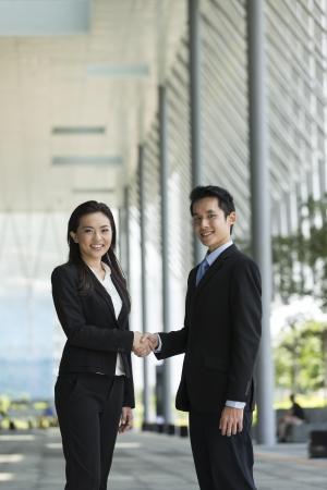 Homme d'affaires chinois et femme d'affaires se serrant la main en dehors du bureau