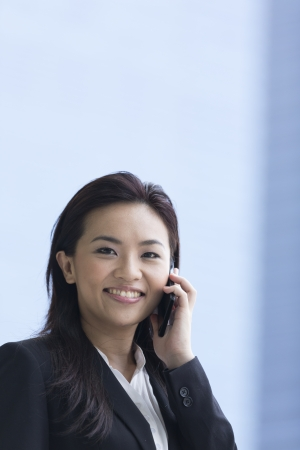 Happy Chinese Businesswoman talking on smart phone. photo