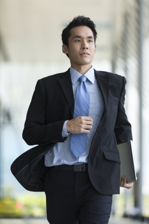 Young Chinese businessman running in a modern city street photo