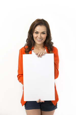 Happy Asian woman with blank board ready for your message. Standing in front of a white wall.