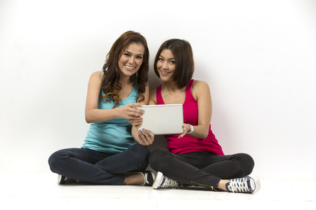 Two happy Asian women using a digital tablet. In front of a white wall.  photo