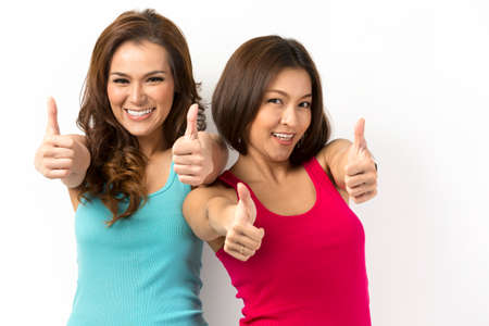 Two happy Asian women with both thumbs up in approval. Leaning against a white wall. photo