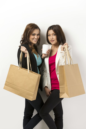 Portrait of a two happy Asian women with shopping bags. Leaning against a white wall photo