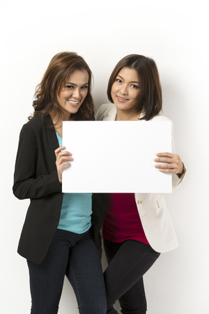 Two happy Asian women with blank board ready for your message. Standing in front of a white wall.  photo