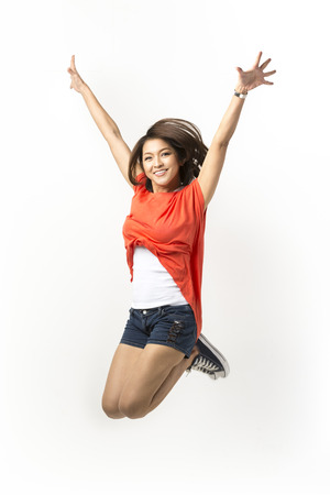 Happy Asian woman jumping for joy. Isolated on a white background.