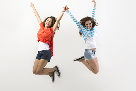 Two excited Asian women jumping in front of a white wall.  Stock Photo