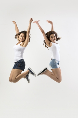 Two excited Asian women jumping in front of a white wall.  photo
