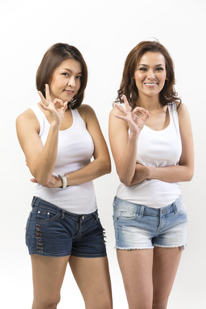 ok symbol: Portrait of two happy Asian Women doing OK symbol. Young fresh Chinese female model Standing in front of a white wall.