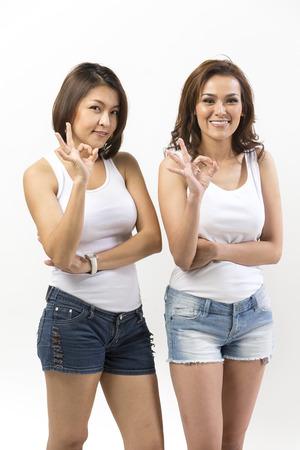 ok symbol: Ritratto di due donne asiatiche felice facendo simbolo OK. Giovane fresco cinese modello femminile in piedi di fronte a un muro bianco.