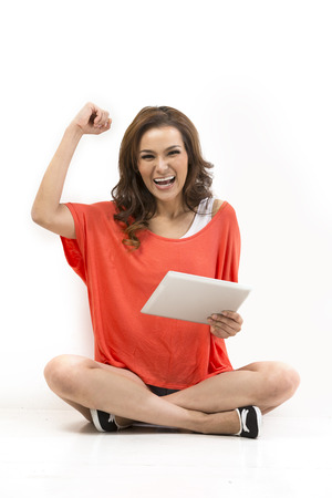 Excited Asian woman holding tablet pc cheering with her arm raised. Sitting on floor and leaning against white wall. photo