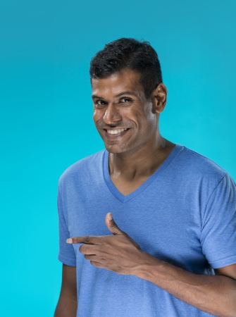 Closeup portrait of a happy Asian Indian man looking to left. Against blue background. photo