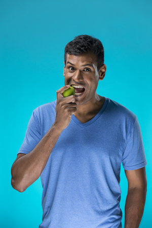 Happy Indian man holding an apple. Healthy eating concept. Young and fresh Asian male model on a blue background. photo