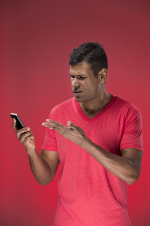 Angry Indian man talking on cell phone. Standing against red background. photo