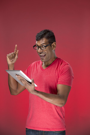 Cheerful Indian man using a tablet PC. In front of red background. photo