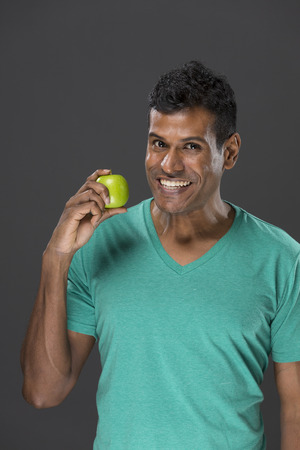 Happy Indian man holding an apple. Healthy eating concept. Young and fresh Asian male model. photo