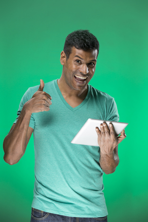 Cheerful Indian man using a tablet PC. In front of green background. photo