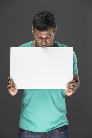 Indian man holding up a banner against a grey background. Cardboard placard is blank ready for your message. photo