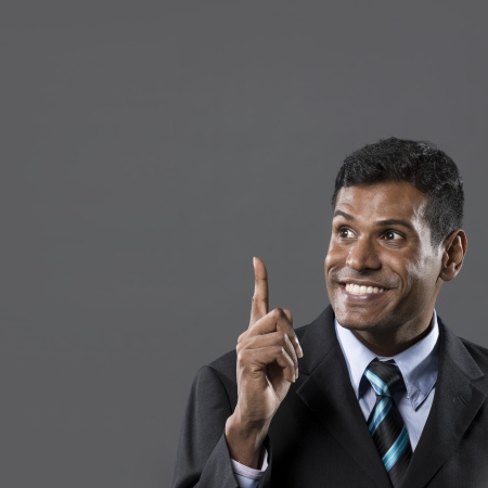 upwards: Portrait of a happy Indian businessman pointing upwards. Light grey background. The photo has been composed so there is plenty of space for your message.