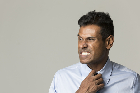 Portrait of a angry Indian business man adjusting his tie. photo