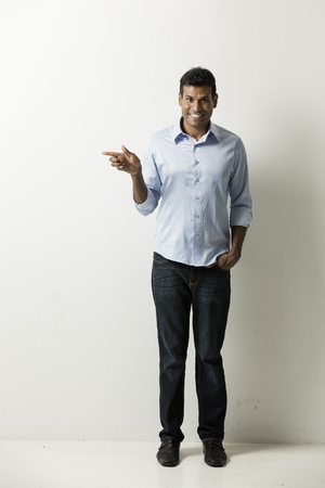 Portrait of a happy Indian man pointing his finger at an empty wall. Space for your message.