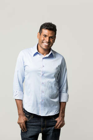 Portrait of a happy Indian man standing in front of a light grey background.  photo
