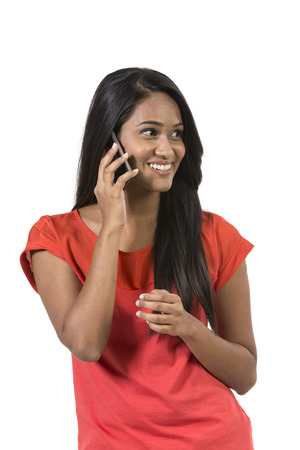 Happy Indian Woman using a smartphone. Isolated over a white background photo