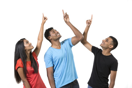 Group of happy Indian friends pointing upwards. Isolated on a white background. photo