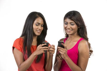 indianen: Gelukkig Indiase vrouwen met behulp van een smartphone. Geïsoleerd over een witte achtergrond
