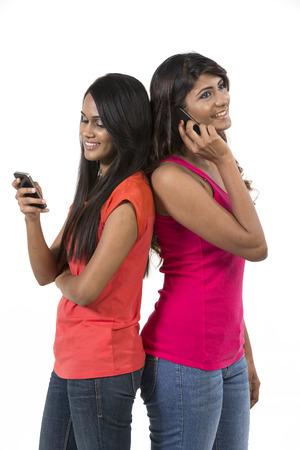 internet movil: Mujeres indias felices que usan un tel�fono inteligente. Aislado en un fondo blanco