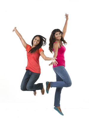 indian girl: Two excited Asian women jumping in front of a white wall.