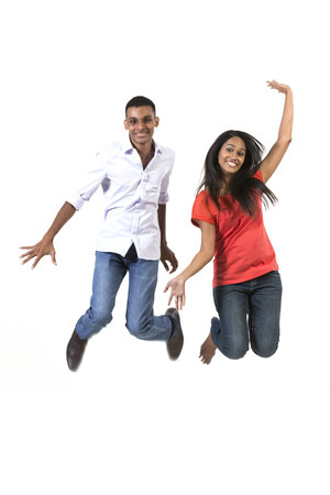 Excited Indian man and woman jumping for joy. Isolated on white background. photo