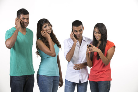 south asian: Group of young Indian friends using their smartphones. Happy Asian people using their cell phones. Isolated on white background.